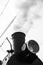 Steam locomotive in steam partial view of the boiler floodligh floodlight and chimney smoke comes out a chimney black and white Royalty Free Stock Photos