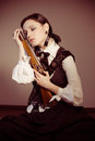 Steam punk beautiful young victorian woman hugging pistol or shotgun eyes closed indoors Royalty Free Stock Image