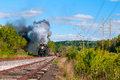 Steam train coming an old time locomotive approaches down the track pulling a passenger excursion Stock Photo