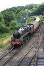 Steam train turning corner black vintage seen from above tree background curved lines Stock Image
