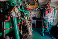 Steam tug vessel engine room of a small harbor with all its engineering parts preserved and painted photo image of driven Royalty Free Stock Photo