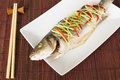 Steamed fish chinese style steamed sea bass garnished ginger chili spring onions Stock Photography