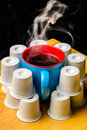 Steaming Coffee Cup surrounded by pods k cups on bamboo Royalty Free Stock Photo