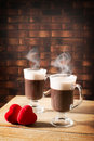 Steaming hot chocolates two mugs of chocolate drinks with love hearts Royalty Free Stock Photos