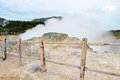 Steaming volcanic krator enclosed by a wooden fence Stock Photography