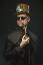 Steampunk man in a hat smoking a pipe. Royalty Free Stock Photo