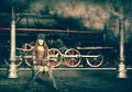 Steampunk and retro futurism style woman traveler sitting on suitcase on platform of railway station near old train clouds of Stock Images