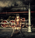 Steampunk and retro futurism style woman traveler sitting on suitcase on platform of railway station near old train clouds of Stock Photo