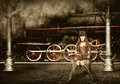 Steampunk and retro futurism style woman traveler sitting on suitcase on platform of railway station near old train clouds of Royalty Free Stock Photos