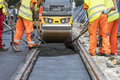 Steamroller workers construct asphalt road and railroad lines Royalty Free Stock Photo