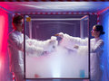 Steamy reactions in sterile chamber two scientists a men and a woman mixing chemicals a labeled as bio hazardous filled with white Stock Image