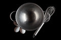 Steel bowl whisker eggs from above on black Royalty Free Stock Photo