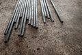 Steel conduits in garage lay on the ground with dim Stock Photo