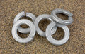 Steel lock washers on sandpaper a small group or a piece of coarse Royalty Free Stock Photo