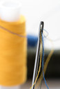 Steel needle with a large oblong eye with threaded needle wide into it threads in the background to blur spool of thread Stock Photo