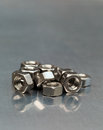 Steel nuts collection of stainless on a metal work bench Stock Images