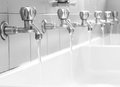Steel taps into a large bathroom in the community Royalty Free Stock Photo
