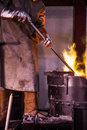 Steel worker raking furnace in an industrial foundry Royalty Free Stock Photo