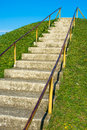 Steep ascend outdoor stairs up onto a green hill into the blue sky Royalty Free Stock Photos