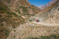 Steep mountain road big tank truck and small car on the precipitous Stock Photo