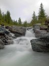 Steep stony stream bed of Alpine brook. Blurred waves of stream running over boulders and stones, high water level after rains Royalty Free Stock Photo