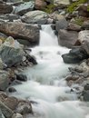 Steep stony stream bed of alpine brook blurred waves of stream running over boulders and stones high water level after rains heavy Royalty Free Stock Images