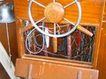 Steering wheel and exposed wiring inside helm of old wooden boat Royalty Free Stock Photo