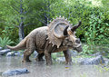 A stegosaurus dinosaur standing in water with woods background.