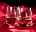 Stemless white wine glasses two served on a red silk table cloth Royalty Free Stock Images
