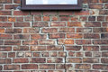Step cracking to brickwork damage in a wall beneath a window as a result of subsidence Stock Photo