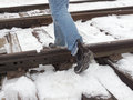 Step over the rails walk on the sleepers in winter in boots Royalty Free Stock Image