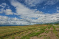 Steppe landscape with road clouds and sky mountains on the horizon Royalty Free Stock Image