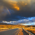 In the steppe runs a gravel road low swirling cloud and flat plain covered orange sunset cloud crosses rainbow storm over Stock Images