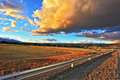 In the steppe runs a gravel road storm over pampas enormous storm cloud and flat plain covered orange sunset Royalty Free Stock Photography