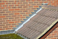 Stepped lead flashing at sloping roof tile abutment to brick wall and flat roof Royalty Free Stock Photography