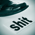 Stepping on shit a man foot wearing a black shoe a signboard with the word written in it Stock Photos
