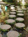 Stepping stones circular creating a beautiful curved pathway across water Royalty Free Stock Photo