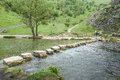 Stepping stones male rambler crosses river dove peak district england via Stock Photo