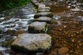 Stepping stones over river and small waterfall Stock Image