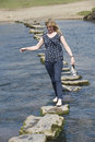 Stepping stones woman barefoot walking across river Royalty Free Stock Photo