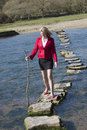 Stepping stones with woman walking across Royalty Free Stock Photo
