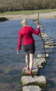 Stepping stones woman walking across river rear view of a in high heels crossing using a tree branch for balance Royalty Free Stock Image