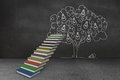 Steps made of books in front of light bulb tree doodle Stock Photo