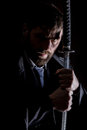 Stern angry businessman in a wool coat with sword in dark background