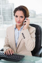 Stern businesswoman phoning in bright office Stock Photography