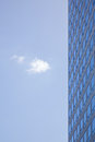 Stern facade of office building and one cloud in blue sky Royalty Free Stock Photo