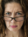 Stern school teacher middle aged female frowning over her glasses Stock Photos