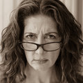 Stern school teacher middle aged female frowning over her glasses Stock Photo