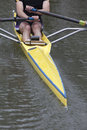Stern of a single scull boat back section rowing and rower s lower body selective focus halfway along Royalty Free Stock Photo