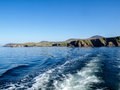 Stern wash from a fishing boat with the slea head on the dingle peninsula in ireland with a clear deep blue sky Stock Images